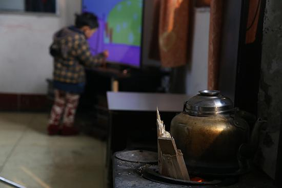 12月15日,临汾市城郊康庄村集中供暖还未接通,一村民家中没有清洁焦,在炉中添了些柴火取暖。
