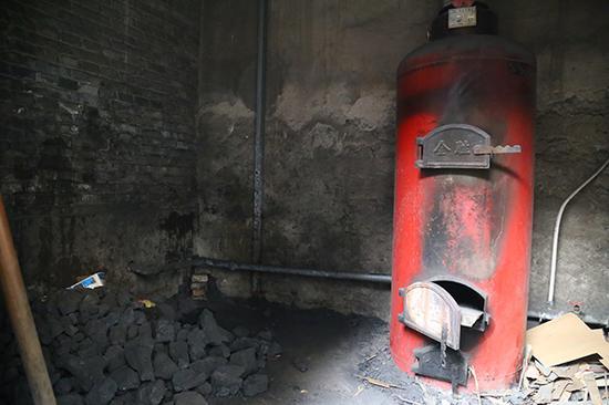 12月15日,临汾市城郊康庄村集中供暖还未接通,村民继续使用燃煤锅炉烧清洁焦取暖。