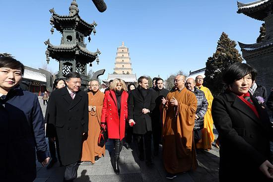 马克龙在参观大雁塔时,聆听寺院僧人做讲解。