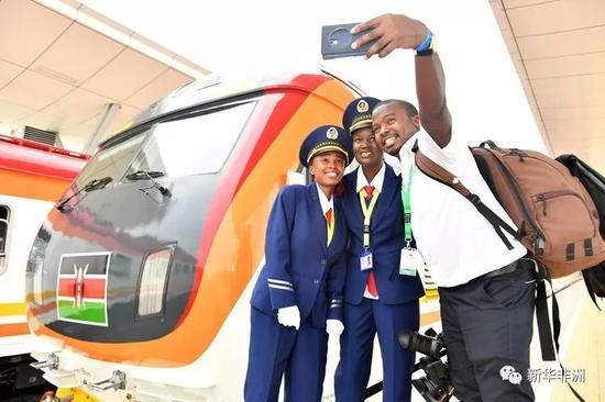 2017年5月31日,在肯尼亚蒙巴萨的蒙内铁路蒙巴萨西站,一名肯尼亚记者和火车司机肯西莉亚(中)、艾丽斯合影留念。新华社记者 孙瑞博摄