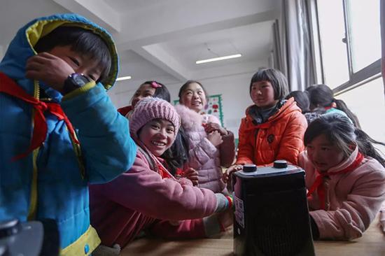 社会爱心人士捐赠的暖风器,孩子下课后围在一起取暖。