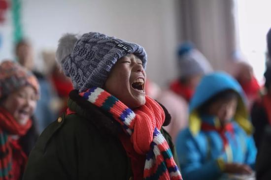 13岁的陶正权领到围巾和帽子后,开心的大笑。