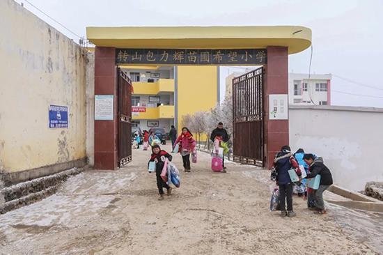 孩子领到爱心物资后,放学回家走出学校大门。