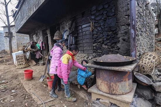 吴世翠、吴双艳回家后煮猪食喂猪,张兴珍(中)家里盖新房这几天都会跟他们一起睡