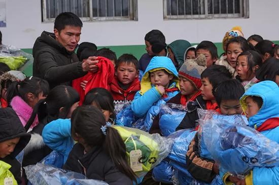 校长付恒给孩子发放爱心衣物。
