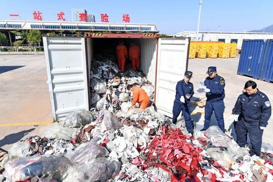 2017年12月21日,厦门海关工作人员在海沧查验场查验走私的进口牛皮革洋垃圾。新华社记者 林善传 摄