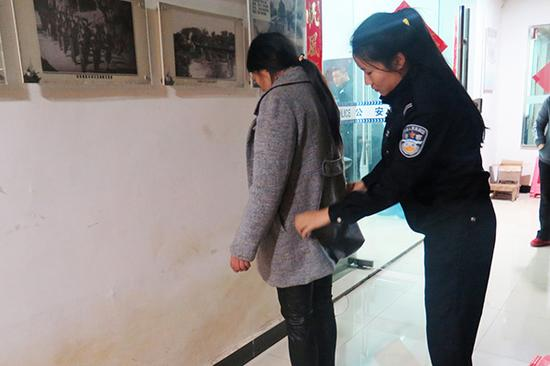 民警正在对抓获人员进行安全检查