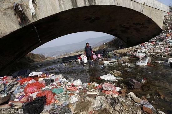 ▲2015年,大别山境内的一条河道的桥下布满各种生活垃圾。 图/视觉中国