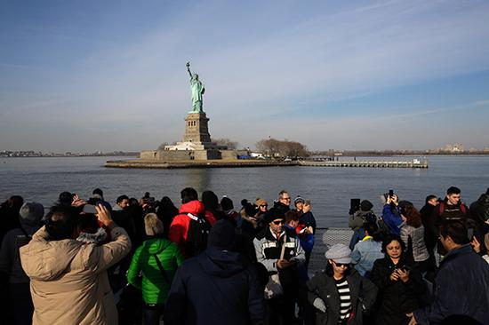 游客们在自由女神像景点拍照留念。视觉中国 图