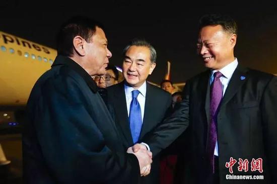 ▲资料图片:2016年10月18日晚,菲律宾总统杜特尔特乘专机抵达北京,开始对中国的国事访问。图为杜特尔特(左)在机场与迎接他的中国外长王毅(中)、中国驻菲大使赵鉴华(右)握手寒暄。