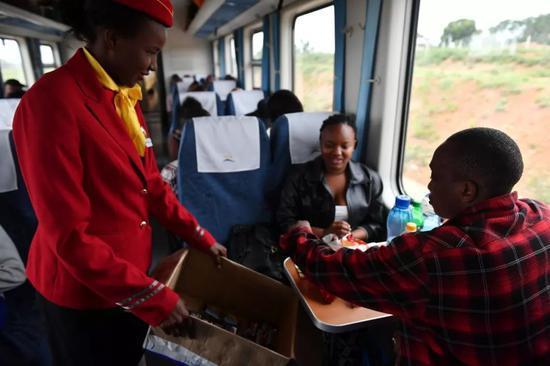 2017年6月1日,在蒙内铁路列车上,乘务员向当地乘客发放饼干。新华社记者孙瑞博 摄