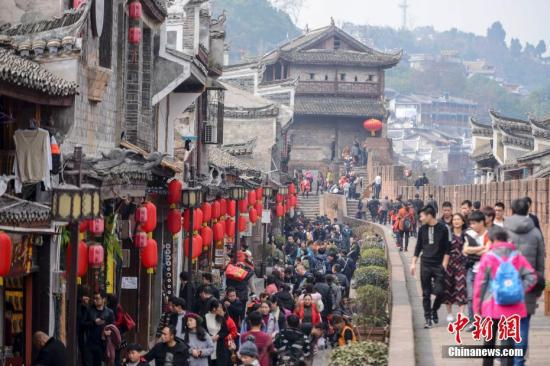 """2月17日,正值农历大年初二,湖南凤凰古城内人头攒动,众多海内外游客选择来到凤凰古城感受新春年味。据凤凰县旅游局统计,仅大年初一当日全县接纳游客4.52万人次,实现旅游收入3296.55万元,同比增长15.90%、6.25%,迎来了新春旅游""""开门红""""。 杨华峰 摄"""