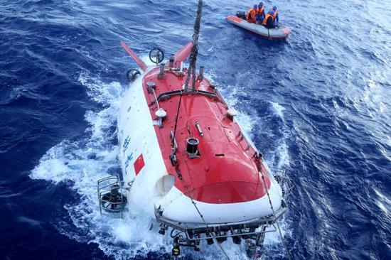 """资料图片:2017年6月13日,""""蛟龙""""号完成中国大洋38航次最后一潜。图为""""蛟龙""""号载人潜水器离开海面。新华社记者刘诗平摄"""