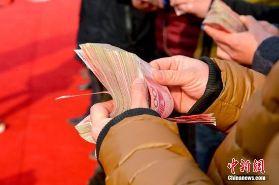 图为农民工正在清点工资。来源:视觉中国
