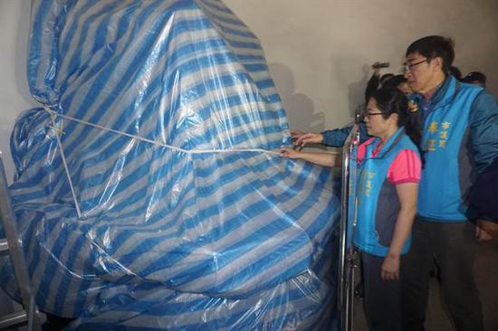 国民党基隆市议会党团正在撤下蒋介石铜像上面的帆布。(图片来源:台湾《中时电子报》)