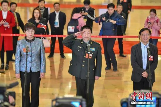 """赵红卫(左)、杨利伟(中)、潘建伟(右)在""""委员通道""""接受媒体采访。 中新社记者 骆云飞 摄"""