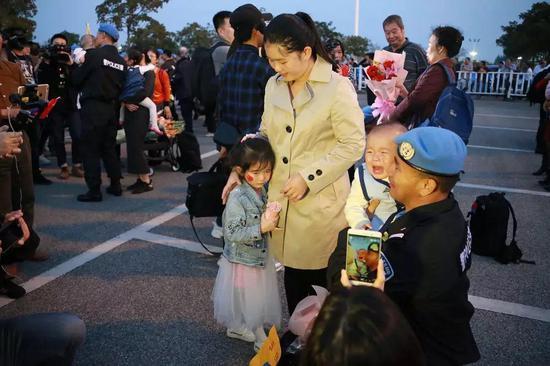 (2018年3月1日,南宁国际机场,秦宗润第一次亲眼见到9个月的儿子,而5岁的女儿也远远躲着他。陈志荣/摄)