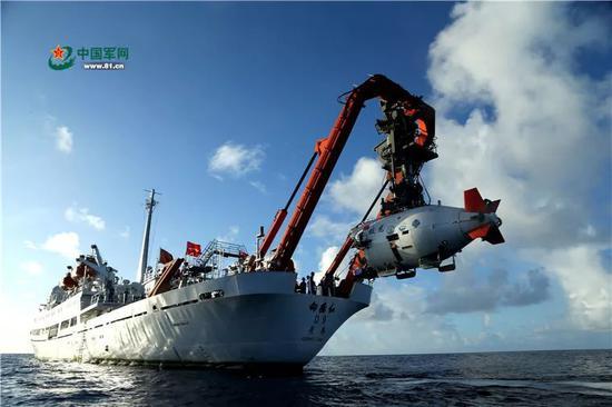 """2017年6月1日,在马里亚纳海沟作业区,""""蛟龙""""号载人潜水器离开""""向阳红09""""科学考察船缓缓进入水中。"""