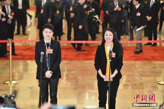 """杨扬(右)在""""委员通道""""接受媒体采访。 中新社记者 骆云飞 摄"""