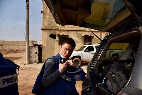 △记者徐德智在战区采访 防弹背心很可能成为危急时刻的救命稻草。