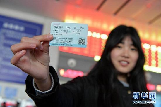 1月3日,春运车票开售首日,在南昌铁路局南昌西站售票处,一位旅客展示她刚刚取到的春运首日火车票(图源:新华网)