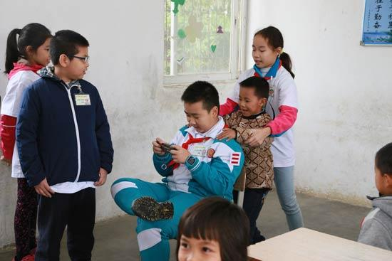 """广东省广州市的小学生到广东清远的山村小学支教,为山村留守儿童上网络安全课。图为""""小讲师""""们演出情景剧模拟孩子们玩游戏时的不良姿势,让学生们纠正。赵晖/摄"""