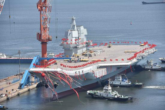 2017年4月26日,我国第二艘航空母舰下水仪式在中国船舶重工集团公司大连造船厂举行。图为航空母舰在拖曳牵引下缓缓移出船坞,停靠在码头泊位。视觉中国供图
