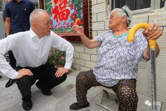 蔡奇蹲下身与86岁的于德凤老人交谈。
