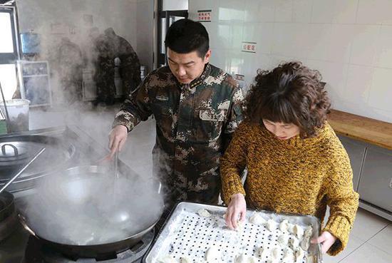 尹丰刚和妻子刘铭俊一起为战士煮饺子。记者孙萌摄