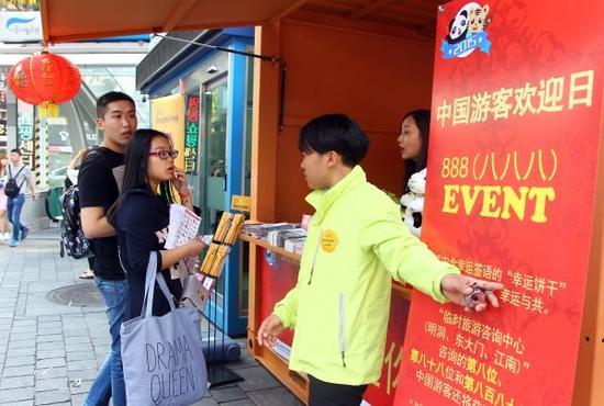 资料图:2015年10月6日是韩国首尔的中国游客欢迎日,中国游客在明洞进行旅游咨询。新华社记者姚琪琳摄