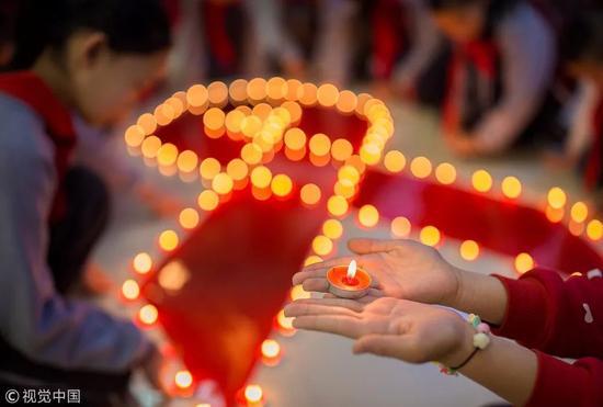 2017年12月1日,呼和浩特市玉泉区石头巷小学学生用蜡烛点亮红丝带,纪念世界艾滋病日。图片来自视觉中国