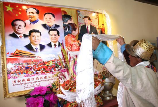 春节和藏历土狗新年初一,曲水县才纳乡吉祥四季村村民土登次仁身穿盛装向挂在客厅的领袖像敬献哈达。记者姚海全摄