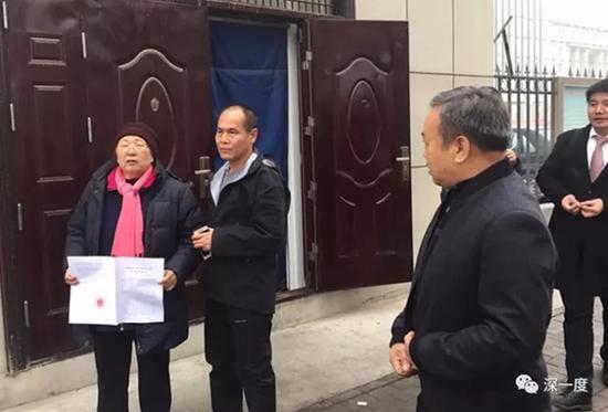 周远母子在法庭外展示判决书。
