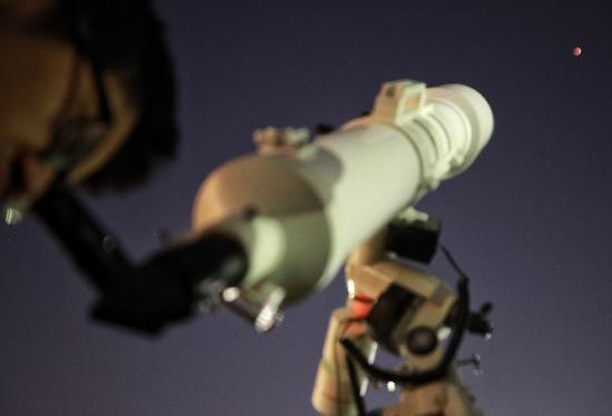 """▲1月31日,北京天文馆,一男士用天文望远镜观看""""红月亮""""。新京报记者 王嘉宁 摄"""