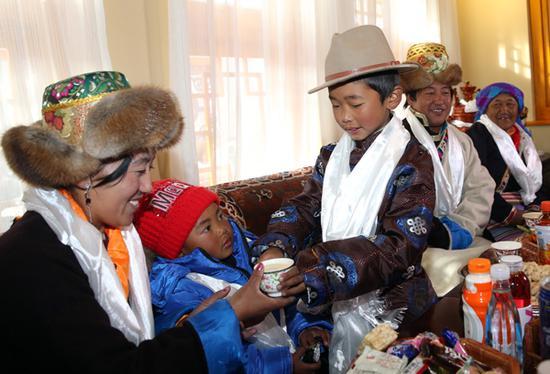 春节和藏历土狗新年初一,吉祥四季村沉浸在欢乐祥和的氛围中,图为家中晚辈向长辈敬茶敬酒。记者姚海全摄