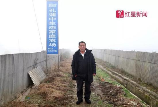 孔蒲中站在自家生态家庭农场牌子底下 本文图片均来自红星新闻