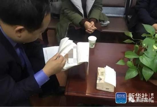 ↑这是1月3日花垣县纪委监察委的工作人员翻看李明所写的交代。