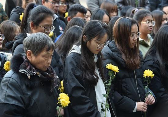 """12月11日,大学生和市民在""""侵华日军南京大屠杀草鞋峡遇难同胞纪念碑""""前祭奠遇难同胞。新华社"""