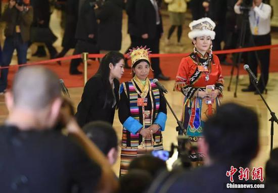 卓嘎(中)在藏语翻译的帮助下接受采访。中新社记者 侯宇 摄