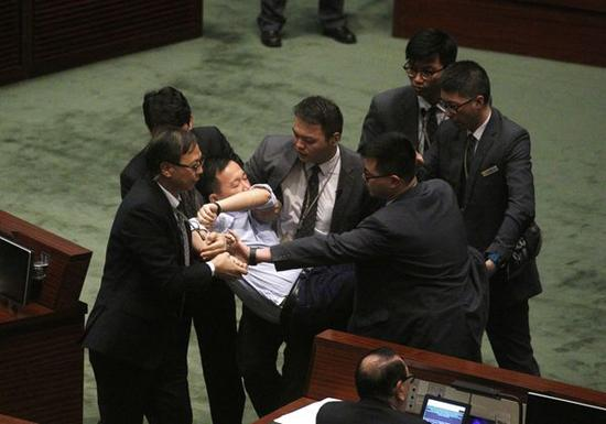 反对派议员冲击主席台,被保安抬走。图片来源于港媒