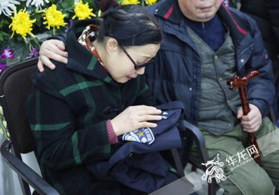 杨雪峰的母亲轻抚着儿子的警服。 记者 刘嵩 摄