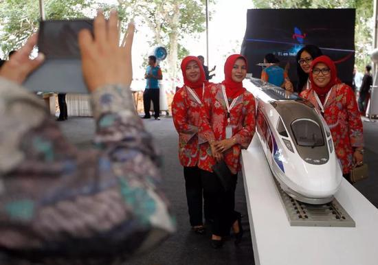 2016年1月21日,在印度尼西亚西爪哇省瓦利尼,参观者在开工仪式上与高铁列车模型合影。(新华社/路透)