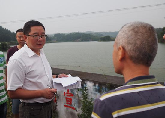 下沉督察期间,督察人员对群众举报的环境信访案件进行抽查,向村干部了解情况。