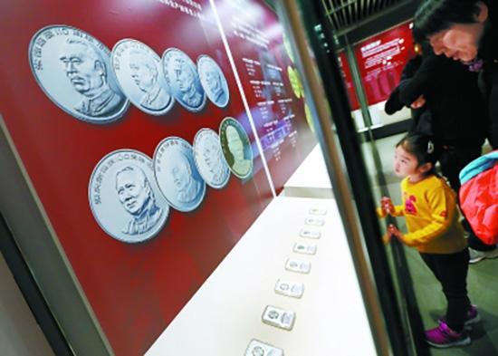 市民在观看我国不同年代发行的人物纪念币。北京日报 图