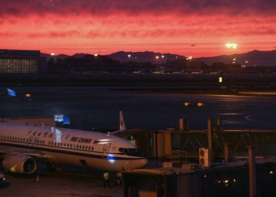 资料图片:2017年5月22日,北京首都机场航站楼外晚霞满天。新华社记者 李贺 摄
