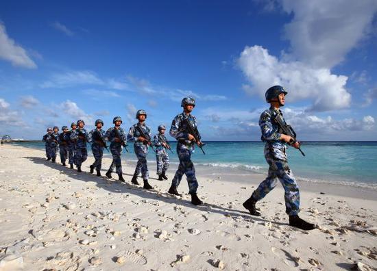 资料图片:2016年1月5日,守卫在南沙群岛永暑礁上的海军官兵在沙滩上巡逻。新华社记者 查春明摄