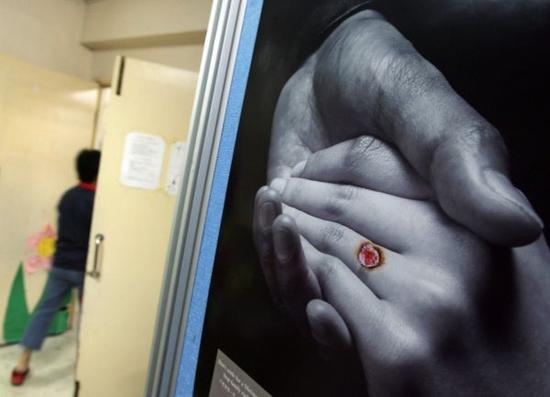 资料图片:一名员工在中国香港一座办公楼内经过反对家庭暴力的宣传海报。新华社发