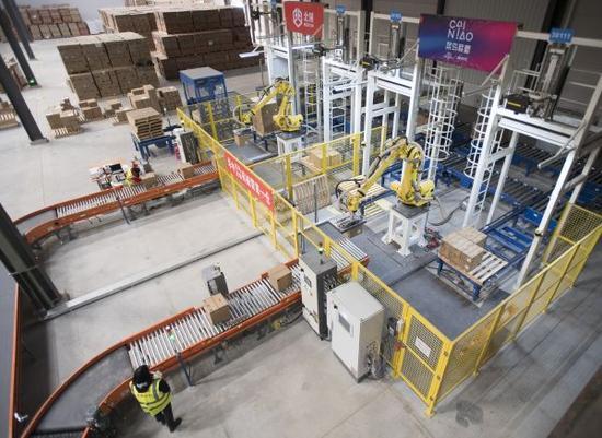 """资料图片:2017年12月26日,在菜鸟网络武汉黄陂物流仓内,机械臂在进行搬运作业。这些机械臂的投入,有助于缓解高峰期货物处理压力,提高发货速度,被工程师亲切地称为""""麒麟臂""""。"""