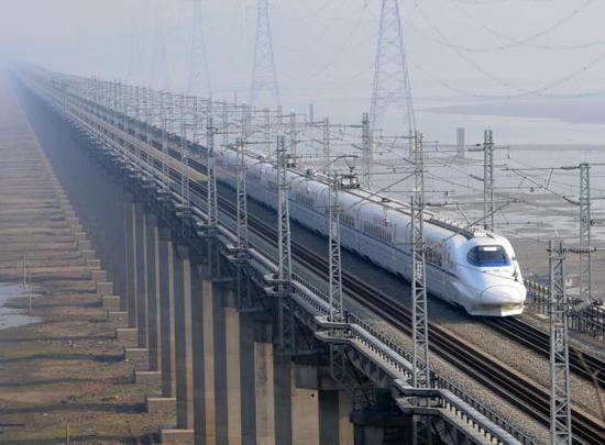 12月12日,江西九江,一列试验动车组行驶在九景衢铁路鄱阳湖特大桥上。 视觉中国 图