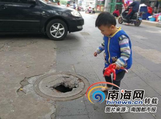 一名两三岁的幼童正在破损的井盖旁边玩耍,非常危险。